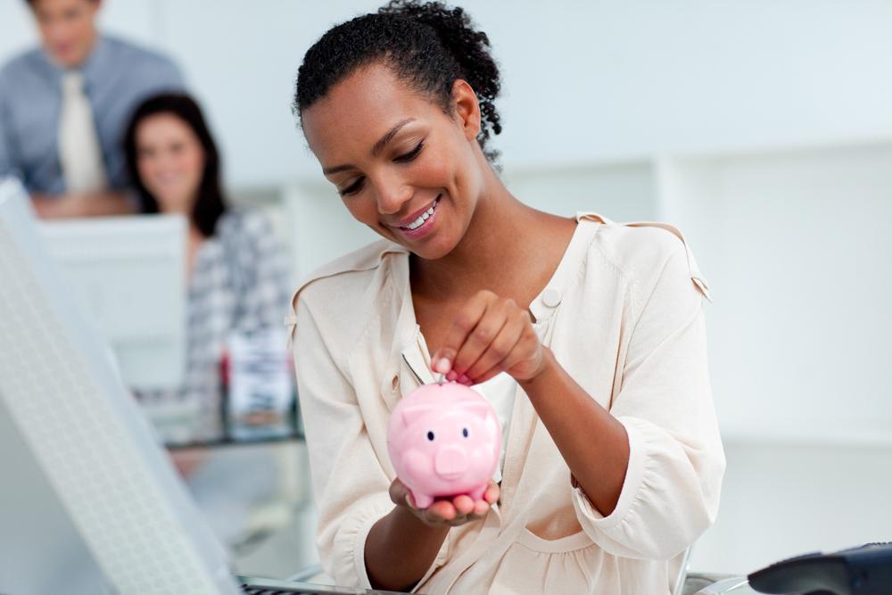 Joyful%20businesswoman%20saving%20money%20in%20a%20piggy-bank%20at%20her%20desk